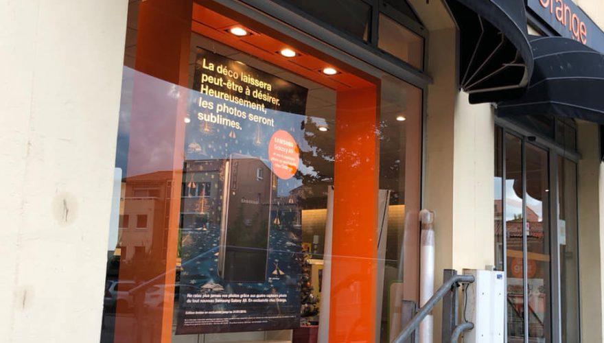 Pose d'un adhésif sur vitrine pour la boutique Orange à Île Rousse par l'équipe Pano Bastia